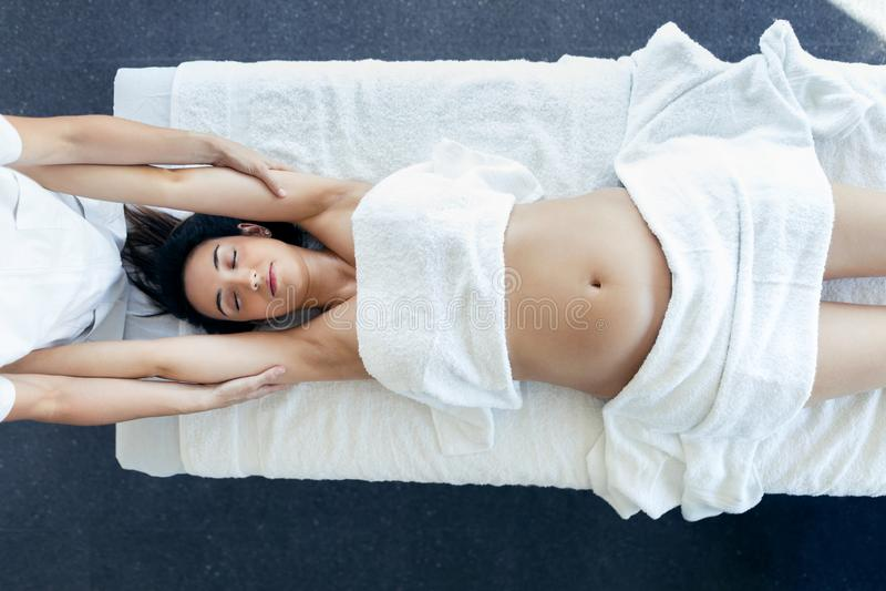 做的理疗师在温泉中心舒展孕妇的胳膊 免版税图库摄影