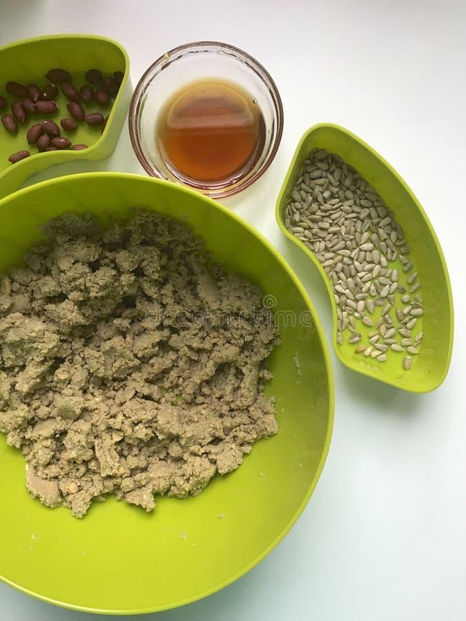 做的自创halva成份 烤花生和种子在容器 附近蜂蜜和切细的成份 库存图片