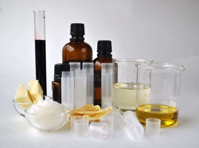 做的自然化妆用品恶黄油、椰子、杏仁、加州希蒙得木和精油成份与管和瓶 免版税库存照片