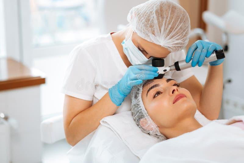 做皮肤考试的熟练的女性皮肤病学家 库存图片