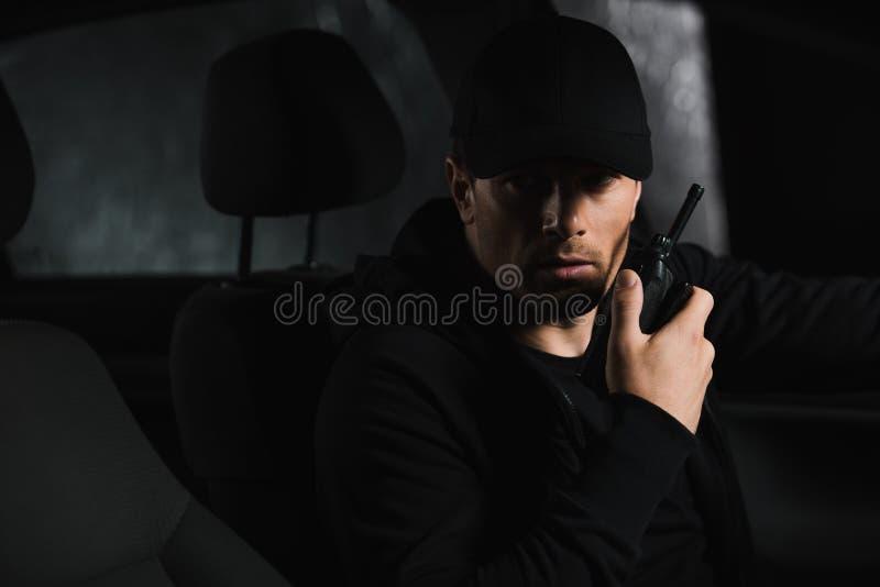 做监视和使用有声电影walkie的盖帽的严肃的男性私家侦探 免版税图库摄影