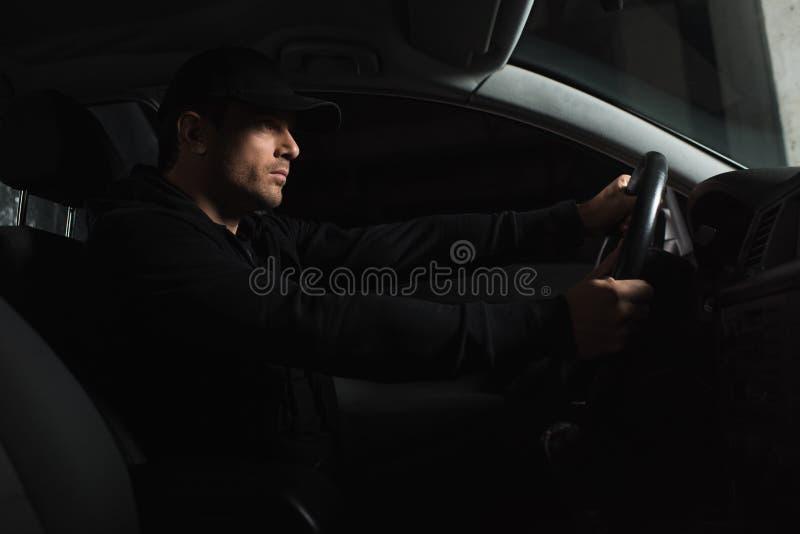 做监视和驾驶的被集中的男性无固定职业的摄影师侧视图  库存照片