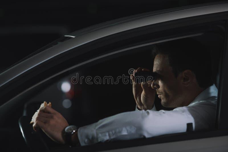 做监视由双筒望远镜和吃三明治的暗中进行的男性代理侧视图  免版税库存图片