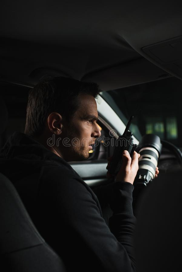 做监视由照相机和使用有声电影walkie的男性无固定职业的摄影师侧视图  免版税库存图片