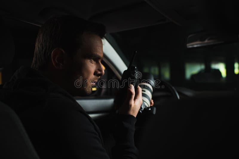 做监视由照相机和使用有声电影walkie的被聚焦的男性无固定职业的摄影师 库存图片