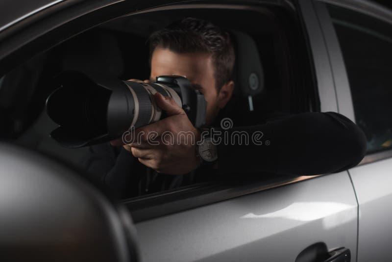 做监视的无固定职业的摄影师由与透镜的照相机从他的 免版税库存图片