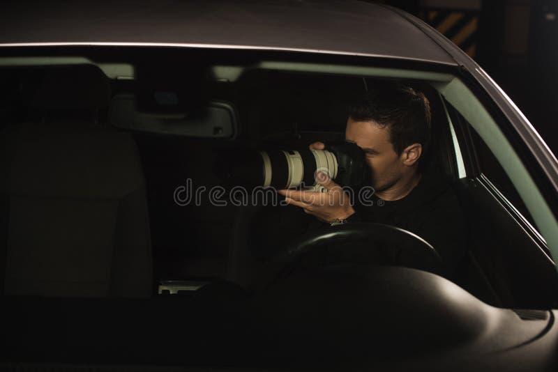 做监视的无固定职业的摄影师由从他的照相机 免版税图库摄影