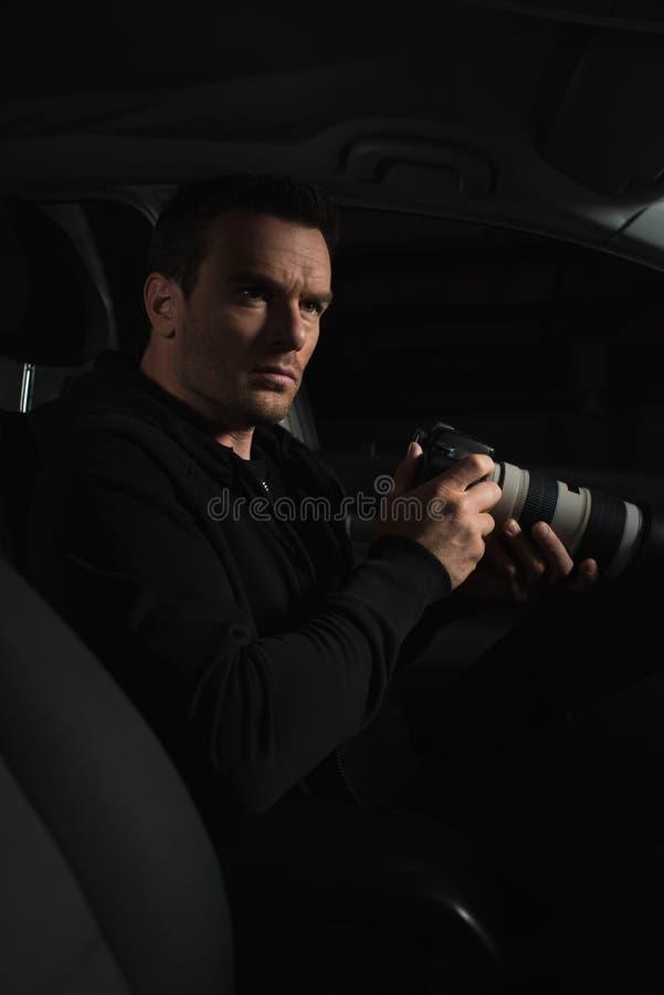 做监视的暗中进行的男性代理由与透镜的照相机从 免版税库存图片