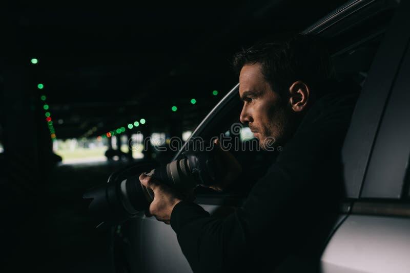 做监视的男性无固定职业的摄影师侧视图由从他的照相机 图库摄影
