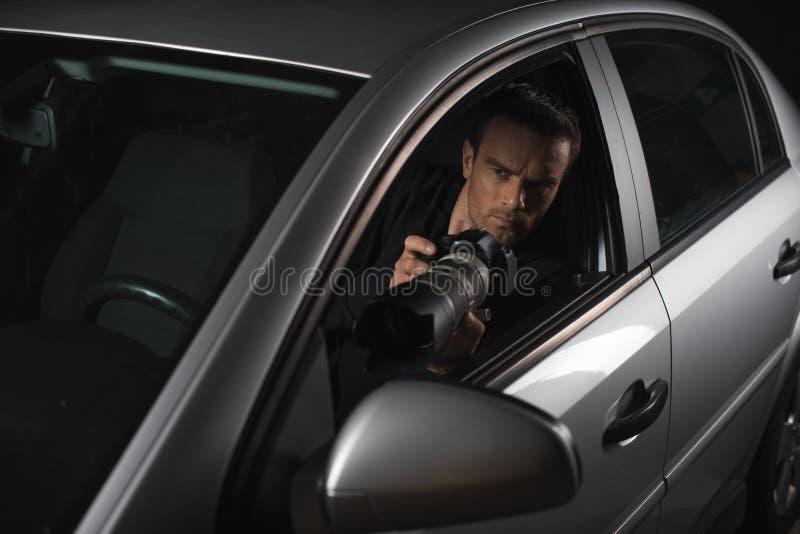 做监视的男性无固定职业的摄影师由与接物镜的照相机从他的 库存照片
