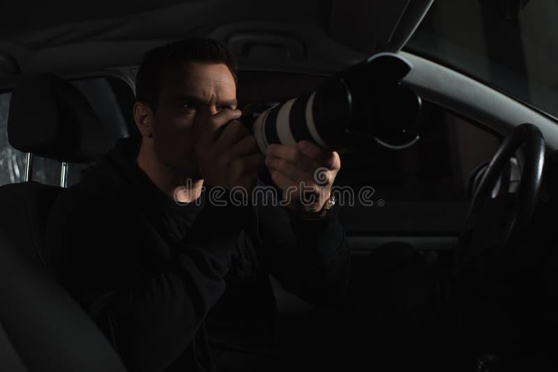 做监视的男性无固定职业的摄影师由从他的照相机 免版税库存照片