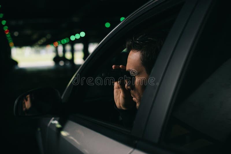做监视的男性无固定职业的摄影师由双筒望远镜从 库存图片