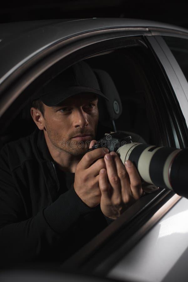 做监视的盖帽的男性无固定职业的摄影师由与接物镜的照相机从他的 库存照片