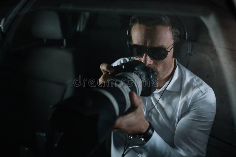 做监视的耳机的男性私家侦探由与接物镜的照相机 免版税图库摄影