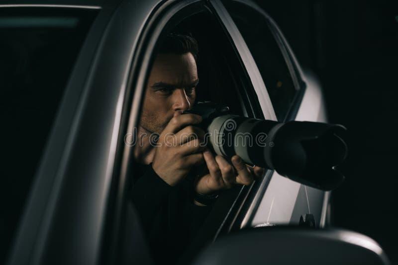做监视的被聚焦的无固定职业的摄影师由从他的照相机 免版税图库摄影