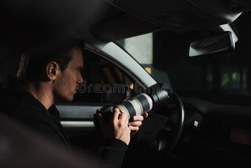 做监视的被集中的男性无固定职业的摄影师由与透镜的照相机从 库存照片