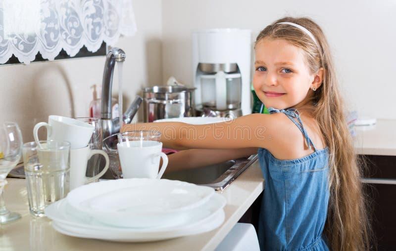做盘的女孩在厨房 免版税库存照片