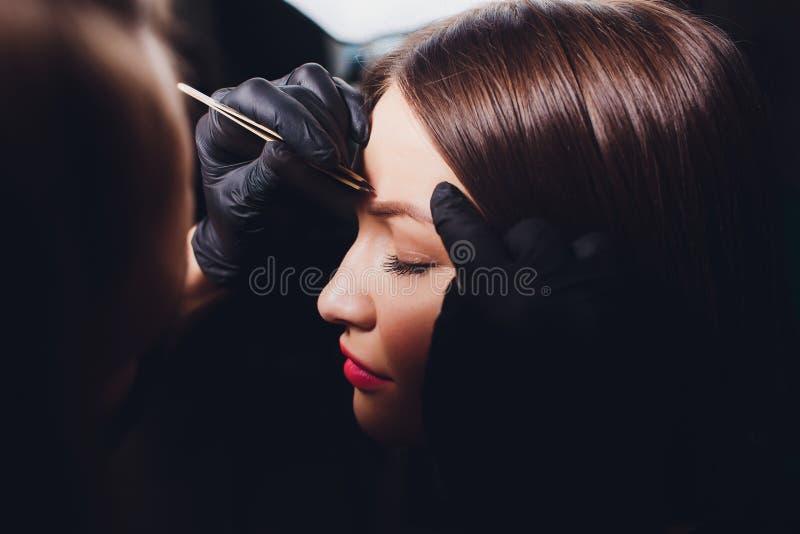 做眼眉的美容师设计 可及面部关心的可爱的妇女发廊 完善的建筑学 库存照片