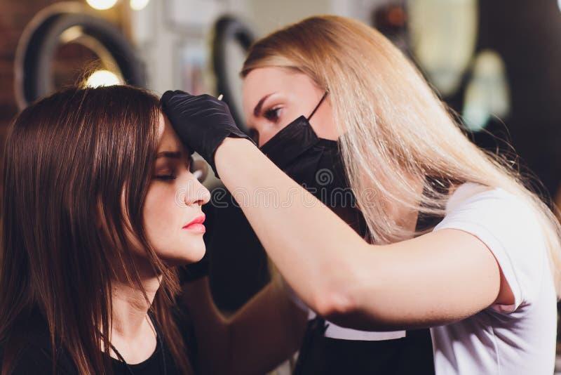 做眼眉的美容师设计 可及面部关心的可爱的妇女发廊 完善的建筑学 免版税库存照片