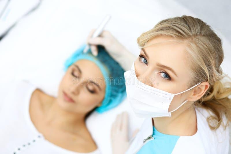 做眼眉纹身花刺的专业美容师在妇女面孔 在美容院,特写镜头的永久眉头构成 Cosmetolog 免版税图库摄影