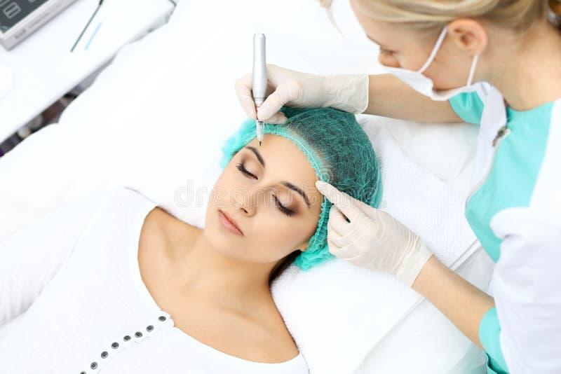 做眼眉纹身花刺的专业美容师在妇女面孔 在美容院,特写镜头的永久眉头构成 Cosmetolog 库存图片