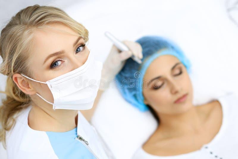 做眼眉纹身花刺的专业美容师在妇女面孔 在美容院,特写镜头的永久眉头构成 Cosmetolog 库存照片
