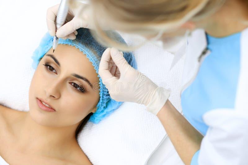 做眼眉纹身花刺的专业美容师在妇女面孔 在美容院,特写镜头的永久眉头构成 Cosmetolog 免版税库存照片