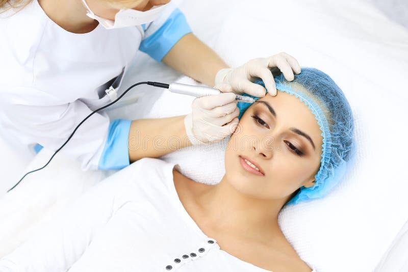 做眼眉纹身花刺的专业美容师在妇女面孔 在美容院,特写镜头的永久眉头构成 Cosmetolog 免版税库存图片