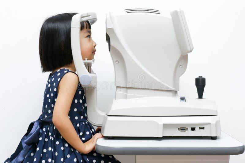 做眼睛检查的亚裔矮小的中国女孩通过自动关于 免版税库存图片