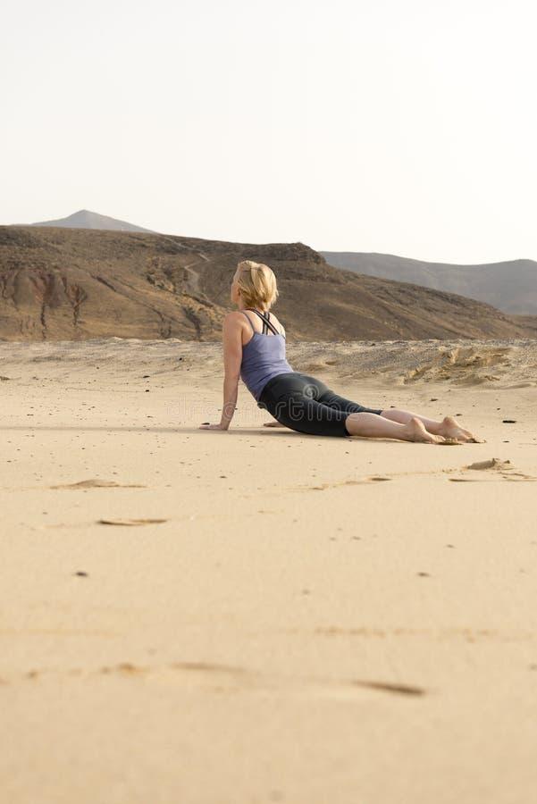 做眼镜蛇在室外沙子的适合的妇女瑜伽姿势 免版税库存图片
