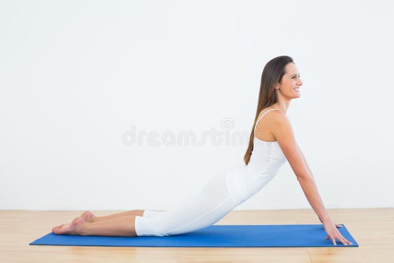 做眼镜蛇姿势的适合的妇女在健身演播室 免版税库存图片