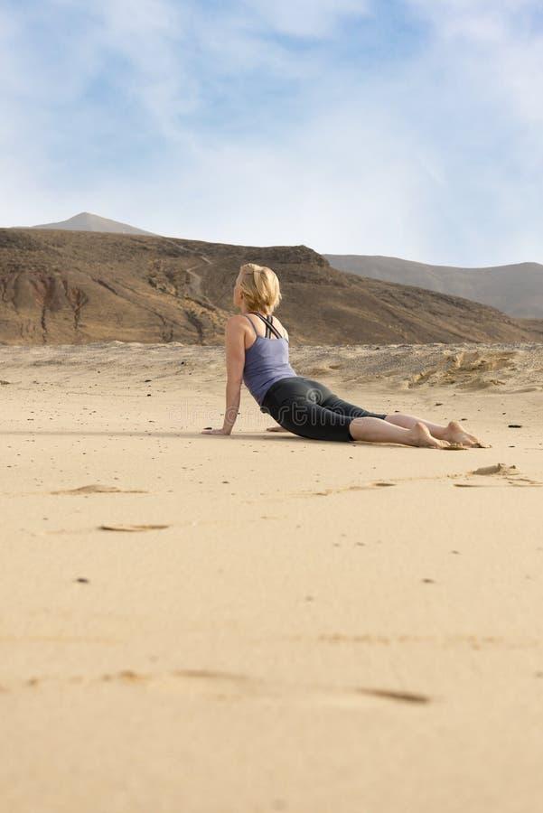 做眼镜蛇瑜伽姿势的适合的妇女在沙漠 免版税库存照片