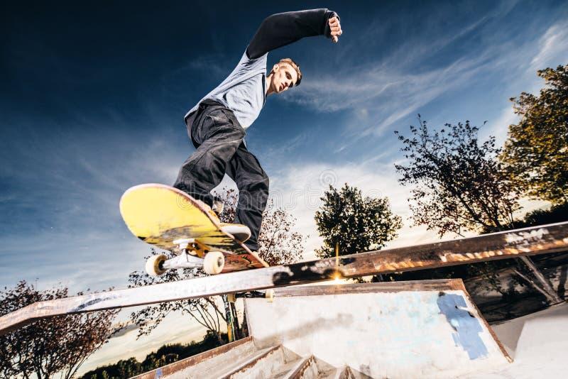 做研磨的年轻溜冰者在Skatepark在日落期间 免版税库存照片