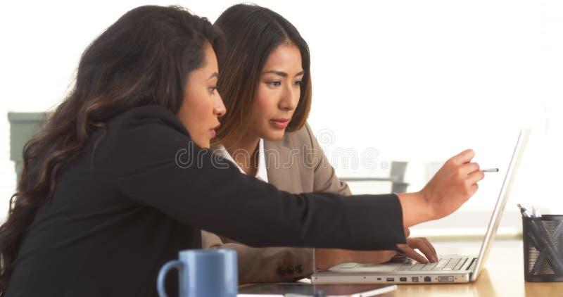 做研究的不同种族的女实业家在书桌 免版税库存照片