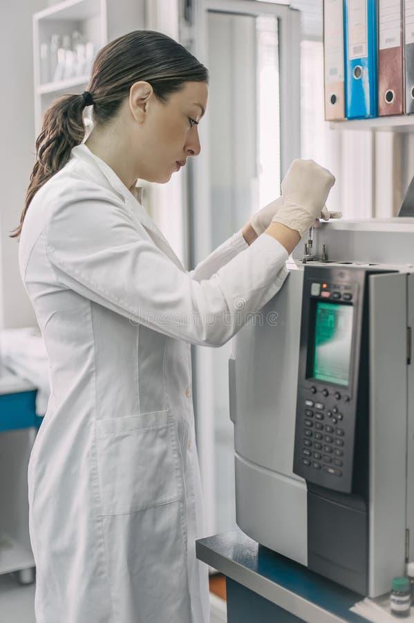 做研究的女性研究员对化学实验室 气体chromat 库存图片