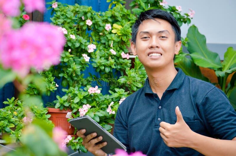 做研究的确信的年轻亚裔男性工作者在室外庭院农场给赞许和拿着片剂计算机 现代的庭院 图库摄影