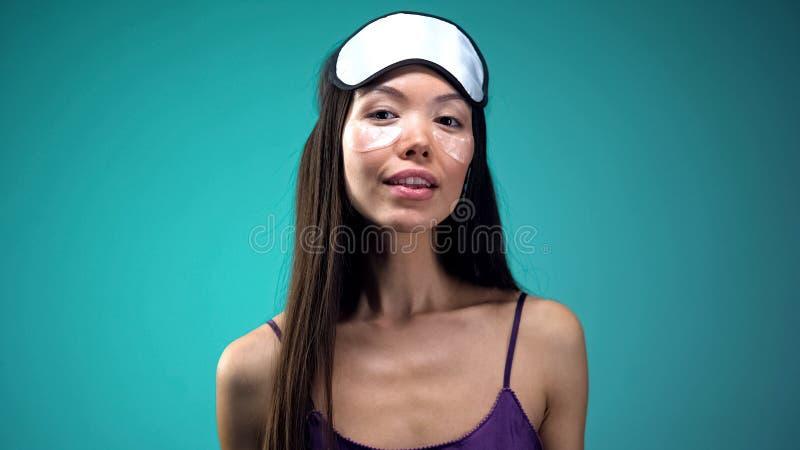做秀丽做法的亚裔妇女在睡觉前,在眼睛下的佩带的补丁 库存照片
