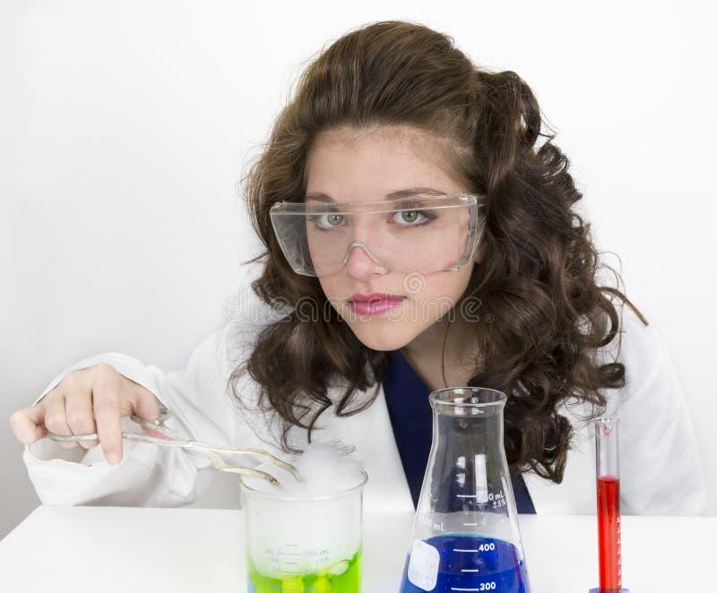 做科学实验的十几岁的女孩佩带的风镜 库存照片