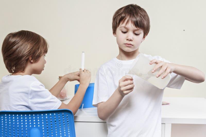 做科学实验的男孩 登记概念教育查出的老 图库摄影