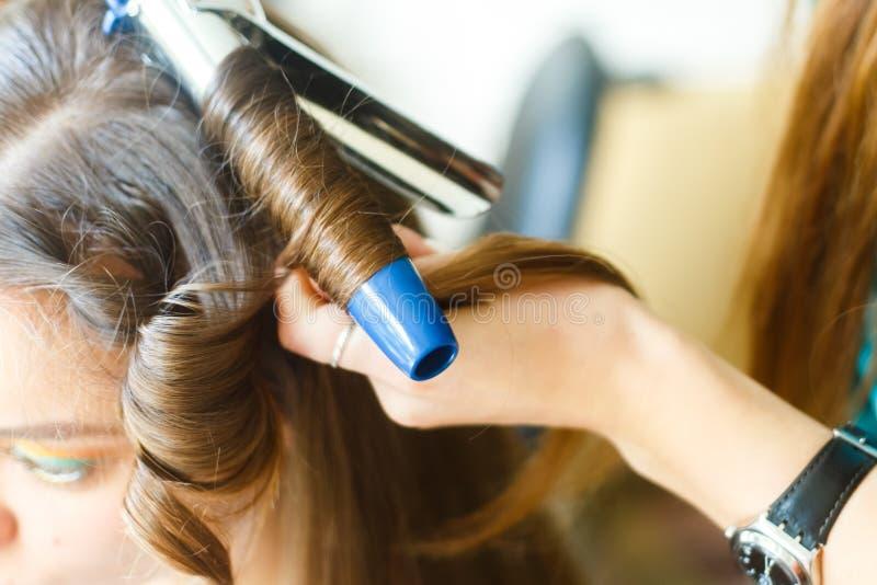 做称呼的美发师特写镜头在一个欢乐晚上婚礼有长的黑发的发型妇女 免版税库存照片