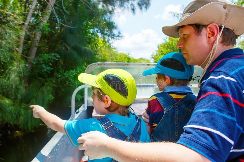 做空气小船的两个小孩男孩和父亲在沼泽地游览停放 免版税库存照片