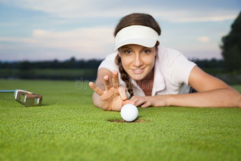 做窍门的女孩高尔夫球运动员在绿色。 库存图片