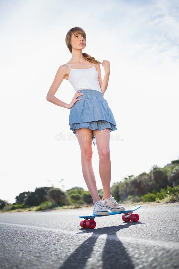 做站立在她的滑板的凉快的溜冰者女孩 库存照片