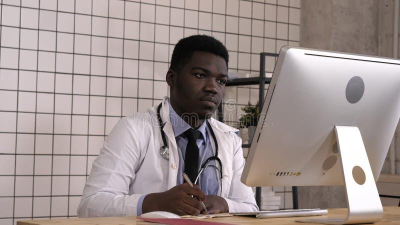 做笔记和查寻某事的年轻非裔美国人的医生在他的计算机 免版税库存照片