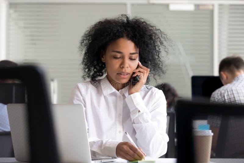做笔记的被聚焦的非裔美国人的妇女,谈话在电话 库存图片