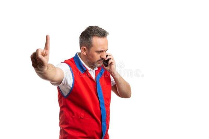 做等待姿态的超级市场雇员谈话在电话 库存图片