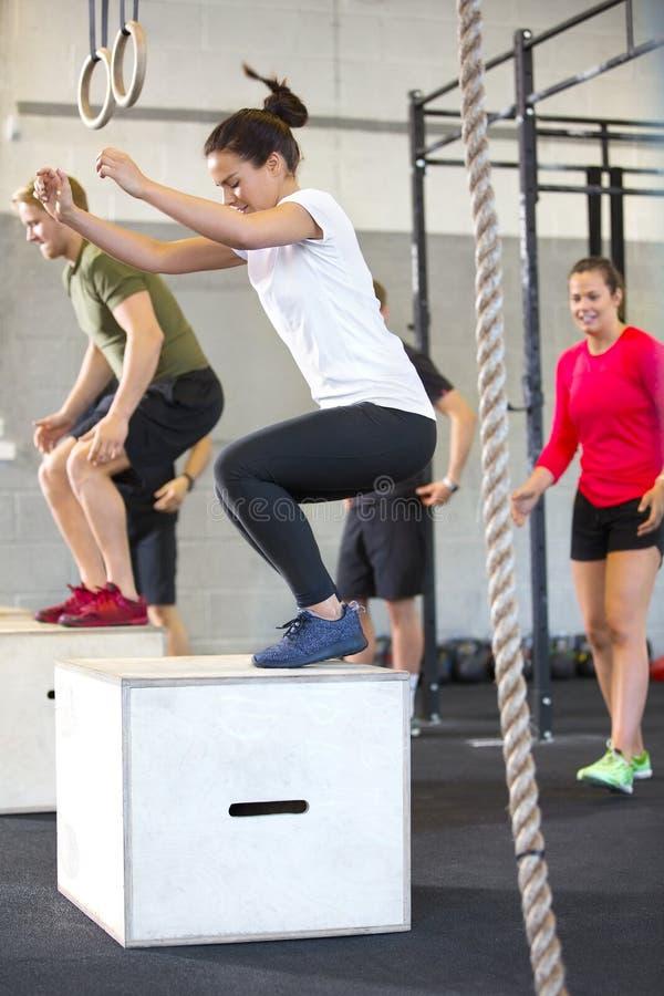 做箱子的坚定的运动员跳跃在健身俱乐部 免版税库存照片