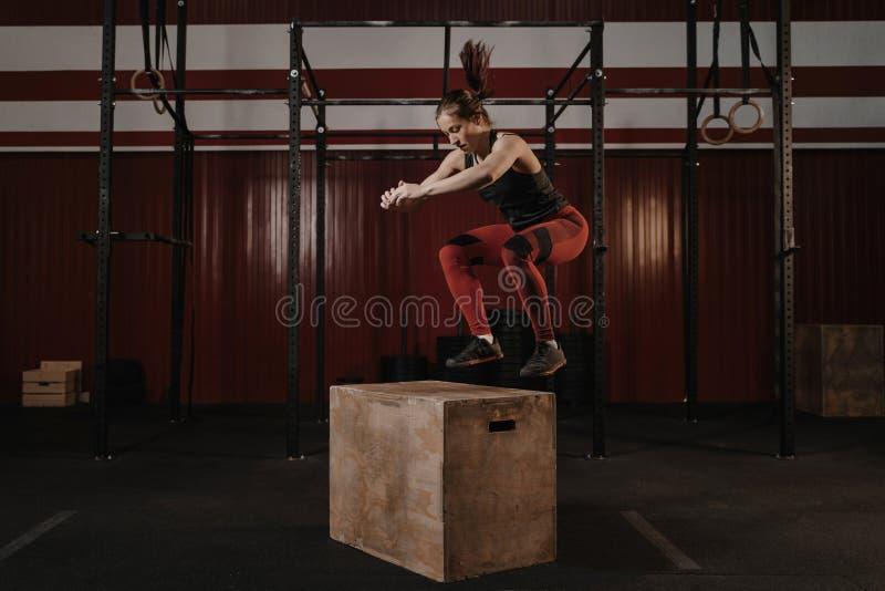 做箱子的年轻crossfit妇女跳跃在健身房 免版税库存照片