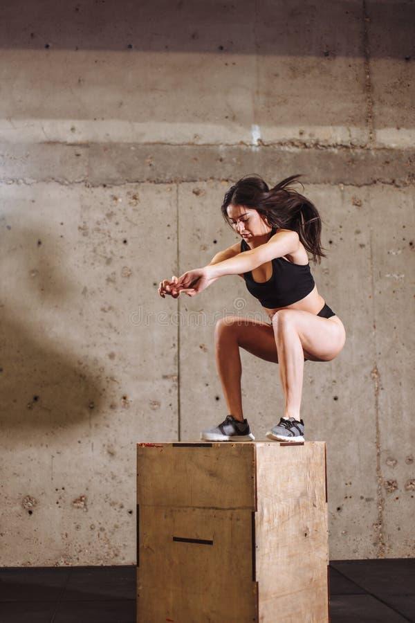 做箱子跃迁锻炼的适合的妇女 做箱子蹲坐的肌肉妇女在健身房 库存图片