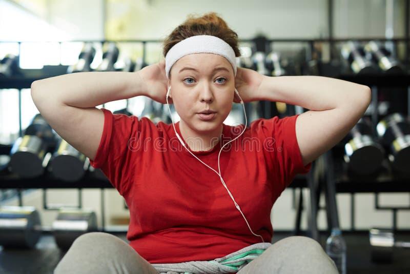 做精力充沛的减重锻炼的肥胖妇女对音乐 图库摄影